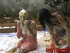 Two dark haired wet and messy babes using strapon outdoor